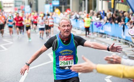 uk money: London, UK - April 23, 2017: Happy Marathon runner cheering by public. Charity money raise.