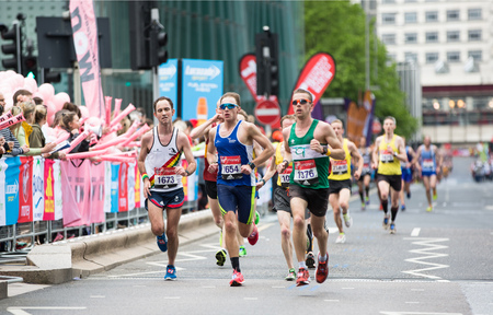 generosa: London, UK - April 23, 2017: London Marathon. Professional sprinters arriving the first in Canary Wharf. People cheering the sportsmen.