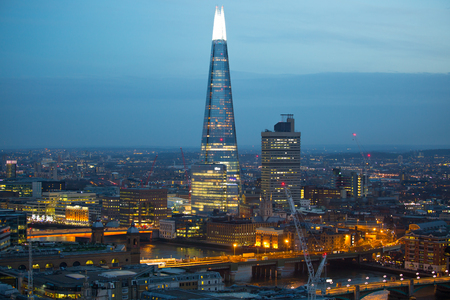 London, UK - December 19, 2016: Shard of Glass and London bridge at night. London at sunset