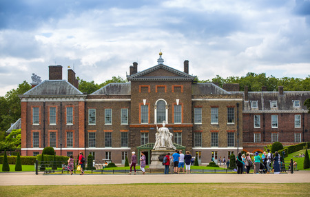 London, UK - September 8, 2016:  Kensington palace, queen Victoria monument in Hyde park view at sunny day with lots of people walking and resting in the park Editorial