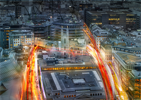 uk money: City of London at sunset and traffic blur lights on busy roads. Technology, transformation and innovation idea.