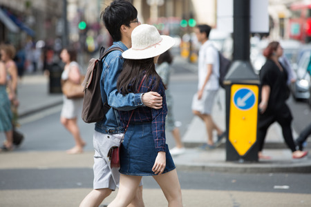 London, UK - August 24, 2016: Young Chinese couple crossing the Piccadilly circus junction Editorial