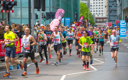 London, UK - April 23, 2017: Lots of people running in London Marathon. People cheering the sportsmen in Canary Wharf area