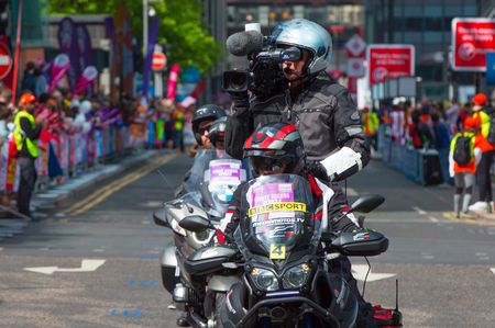London, UK - April 23, 2017: Camera man on the bike at London Marathon. People cheering the sportsmen in Canary Wharf