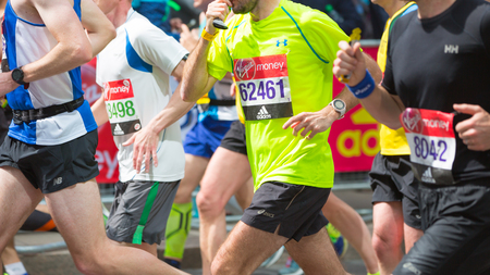 London, UK - April 23, 2017: Close up body of London Marathon runners. People cheering the sportsmen in Canary Wharf aria