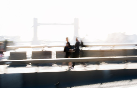 London, UK. Blurred image of office workers crossing the London bridge in early morning on the way to the City of London. Tower bridge at the background. Rush hours