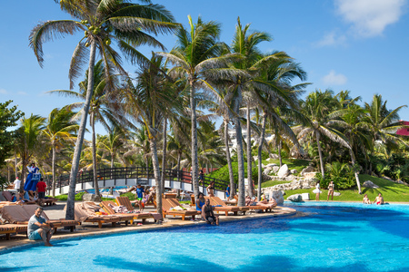 Mexico, Cancun - February 15, 2018: Grand Pyramid hotel swimming pool with palms and sunbeams. People chilling out by the water. Editorial