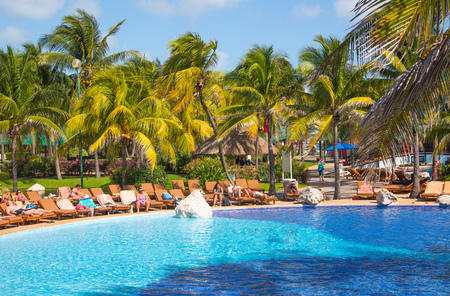Mexico, Cancun - February 15, 2018: Grand Pyramid hotel swimming pool with palms and sunbeams. People chilling out by the water. Redactioneel