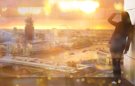 Young woman looking over the City of London at sun set 新聞圖片