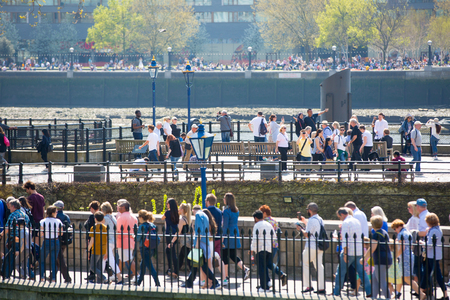 London, UK - April 19, 2018: Lots of people crossing the footbridge near the Tower of London. Rush hours concept