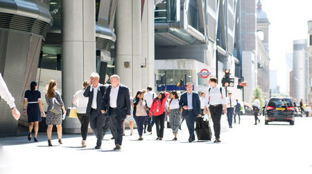 LONDON, UK - 26 June, 2018: Group of business people walking in the city against of sun light. Beautifully lit up street by the sun, City of London modern busy concept.
