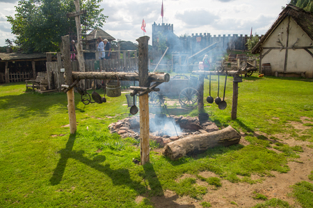 Essex, UK - 31 August, 2018: Cooking fire on the main square Norman village reconstruction, dated back to 1050. Educational centre for kids with demonstration of everyday life and skills medieval time