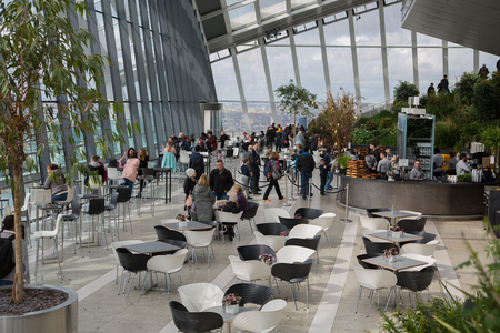 London, UK - 25 April, 2019: Public garden on the 34 floor of skyscraper with cafe and great view of London. People enjoying the morning coffee.