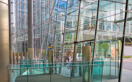 London, UK - 25 April, 2019: Glass windows of the ground floor office building with beautiful reflections and  view on Canary Wharf Editorial