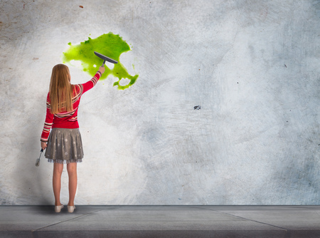 Little girl  standing in front of the wall and paint with the bright colours. Background for your text or advertisement. drawing a large business idea sketch with a yellow light bulb on a concrete wall