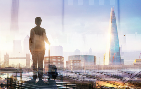 Traveller with suit case looking over the City of London at sunset. Business and travel concept image