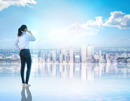 Business woman looking at the City of London.  Canary Wharf business and banking aria. Business, success and strategy concept
