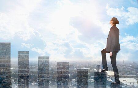 Jonge vrouw klimt op de groeibalken en kijkt positief naar de toekomst. Blauwe lucht en zonneschijn. Bedrijfs-, succes- en strategieconcept Stockfoto