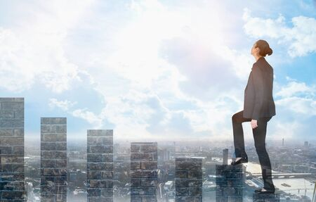 Junge Frau klettert auf die Wachstumsbalken und blickt positiv in die Zukunft. Blauer Himmel und Sonnenschein. Geschäfts-, Erfolgs- und Strategiekonzept Standard-Bild