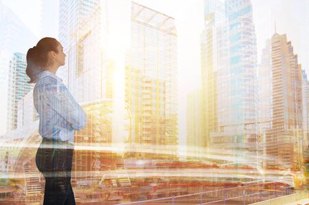 Business woman looking at the modern skyscrapers and sunset. Global business,  success and strategy concept