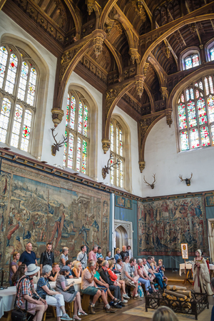 London, UK - July 29, 2019:  Interior of the Hampton court 17th century. People listening the story in the west hall of the court. Editorial