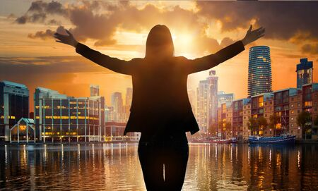 Young woman silhouette with wide open arms agains of London City view at sunset.
