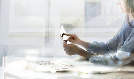 Mujer que trabaja en la oficina contra la ventana, iluminada con rayos solares. Cerrar las manos sosteniendo la pluma trabajando en calculadora, tableta, teclado, calculando datos comerciales. Foto de archivo