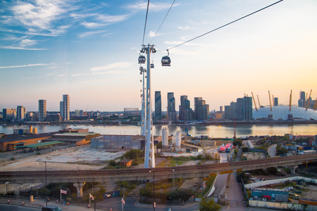 London, UK - August 27, 2019: Cable cars  above London. View includes Excel exhibition complex, docks and river Thames at sunset. Foto de archivo - 129659446