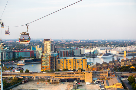 London, UK - August 27, 2019: Cable cars  above London. View includes Excel exhibition complex, docks and river Thames at sunset. Foto de archivo - 129659449