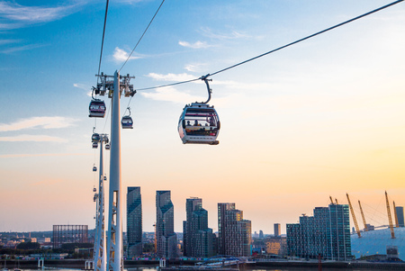 London, UK - August 27, 2019: Cable cars  above London. View includes Excel exhibition complex, docks and river Thames at sunset. Foto de archivo - 129659453