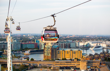 London, UK - August 27, 2019: Cable cars  above London. View includes Excel exhibition complex, docks and river Thames at sunset. Foto de archivo - 129659460