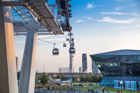 London, UK - August 27, 2019: Cable cars  above London. View includes Excel exhibition complex, docks and river Thames at sunset. Foto de archivo - 129659464