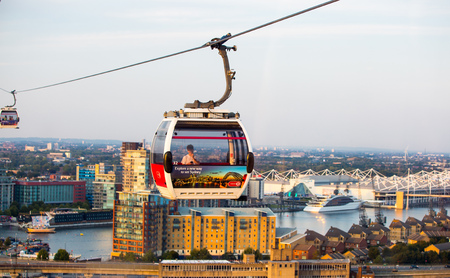 London, UK - August 27, 2019: Cable cars  above London. View includes Excel exhibition complex, docks and river Thames at sunset. Foto de archivo - 129659466