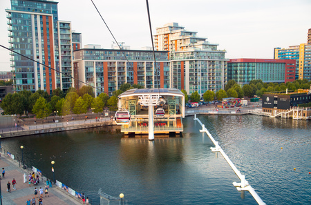 London, UK - August 27, 2019: Cable cars  above London. View includes Excel exhibition complex, docks and river Thames at sunset. Foto de archivo - 129659468