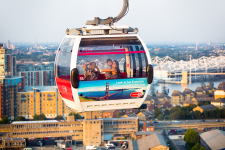London, UK - August 27, 2019: Cable cars  above London. View includes Excel exhibition complex, docks and river Thames at sunset. Foto de archivo - 129659469