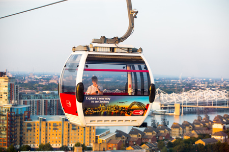 London, UK - August 27, 2019: Cable cars  above London. View includes Excel exhibition complex, docks and river Thames at sunset. Foto de archivo - 129659472
