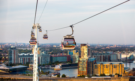 London, UK - August 27, 2019: Cable cars  above London. View includes Excel exhibition complex, docks and river Thames at sunset. Foto de archivo - 129659481