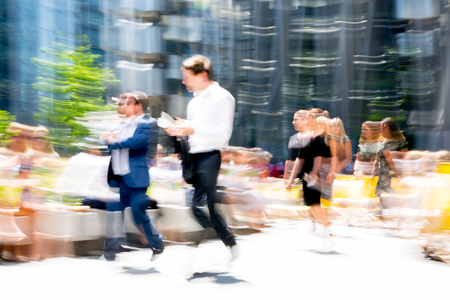 London, UK - April 19, 2018: Motion blur of business people walking in the City of London.