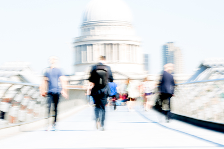 London, UK - April 19, 2018: Motion blur of  people crossing the Millennium bridge.  St. Paul's cathedral at the background Foto de archivo - 129659483