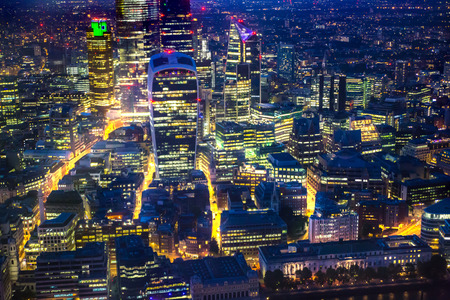 City of London business and banking area at nigh with beautiful lit up skyscrapers and streets. View includes London Bridge and river Thames. London, UK