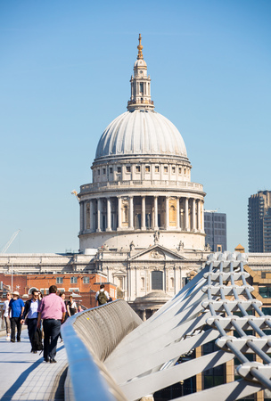 London, UK - April 19, 2018: People crossing the Millennium bridge.  St. Pauls cathedral at the background Editorial