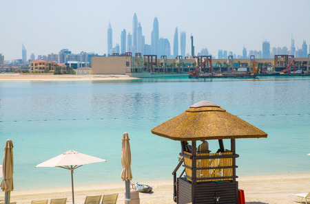 Dubai, UAE, United Arab Emirates - 28 May, 2019: Atlantis Aquaventure water park beach with white sand, locates on the Palm Jumeirah. Skyscrapers of Dubai Marina at the distance