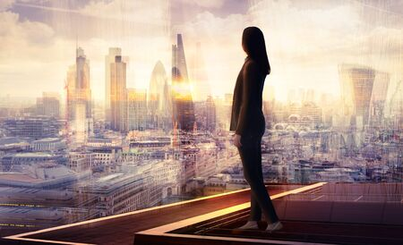 Young woman looking over the City of London at sunset. Beautiful city background in gentle light. Future, freedom, business success and new opportunity concept Reklamní fotografie