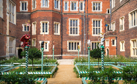London, UK - July 29, 2019: Inner yard of the Hampton court with coat of arms, Dragons sculptures, representing power and authority. Historical place going back to Tudors time locates in West London