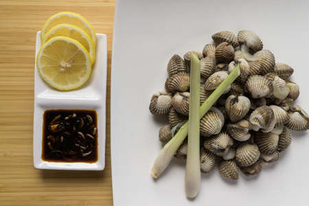Delicious boiled fresh cockles served with spicy & delicious seafood sauce with lemon and lemon grass. Top view on white plate & wooden background.