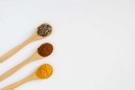 Turmeric, Paprika and Black Pepper ground in wooden spoon over white background. Banco de Imagens