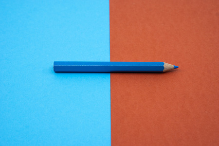 Blue color pencil color isolated on blue and red background. Selective focus.