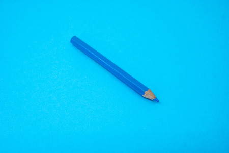 Blue color pencil color isolated on blue background. Selective focus.