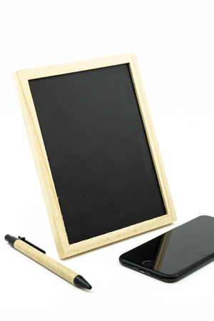 Tripod standing small blackboard, pen and black mobile phone isolated on white background. Imagens