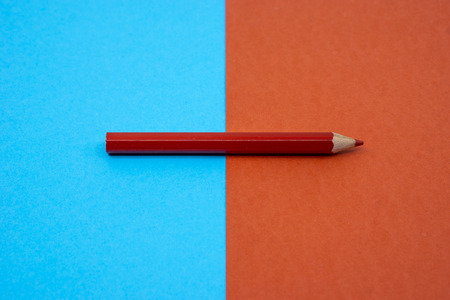 Red color pencil color isolated on blue and red background. Selective focus. Banco de Imagens